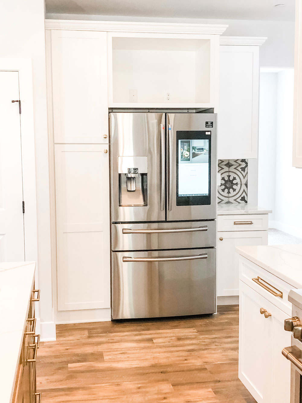 Picture from a custom home tour of a kitchen. This picture shows a refrigerator surrounded by white cabinetry. The fridge is a smart fridge with a screen like a tablet or phone.