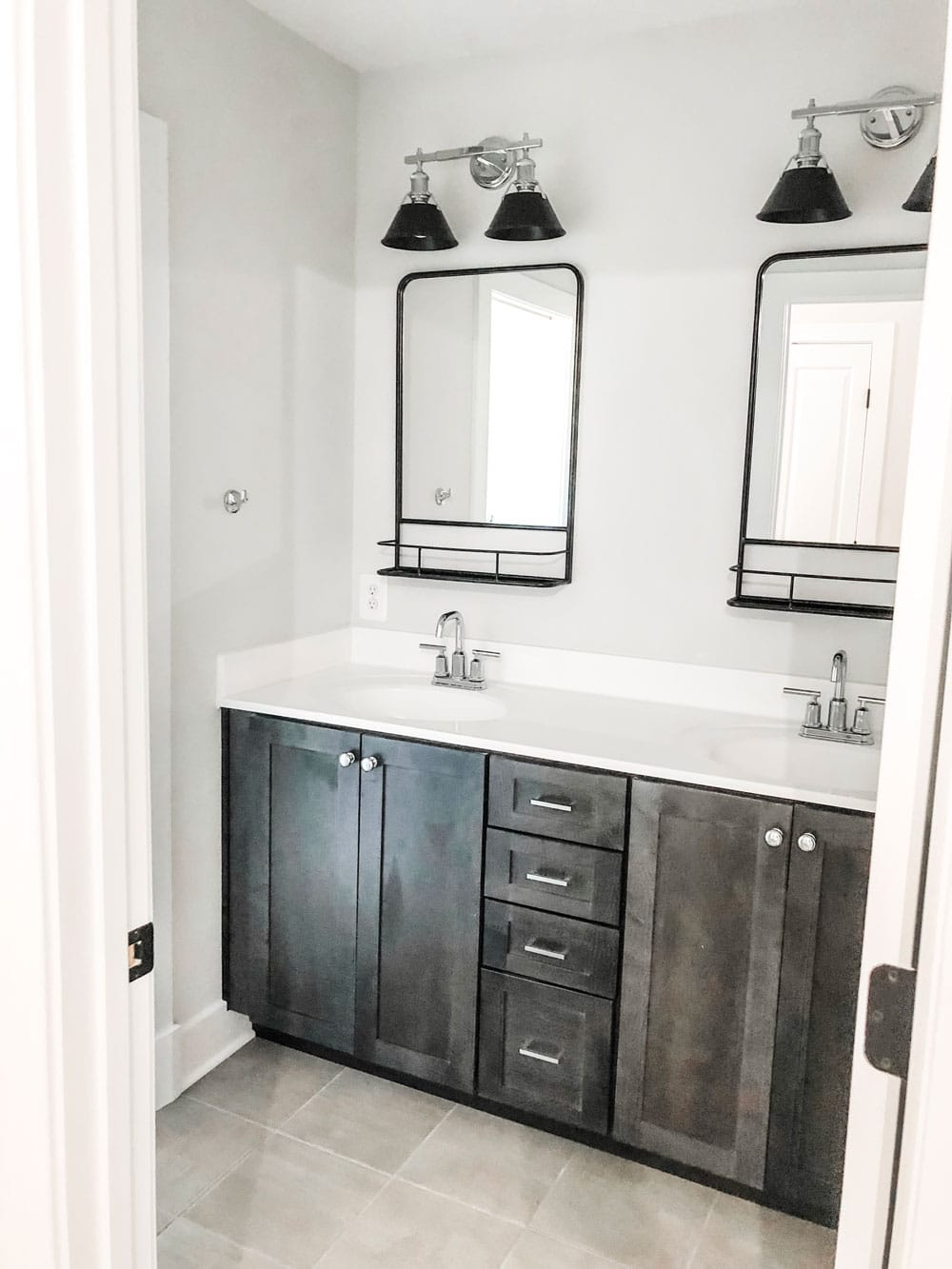 Custom home tour photos. This photo shows a double bath vanity. The bath cabinet is a dark wood grain and it has a solid white marble top. There are two black mirrors - one above each sink. There is also a light above each sink that is a two light fixture with black shades and chrome for the rest of the fixture. There are chrome handles and chrome faucets.