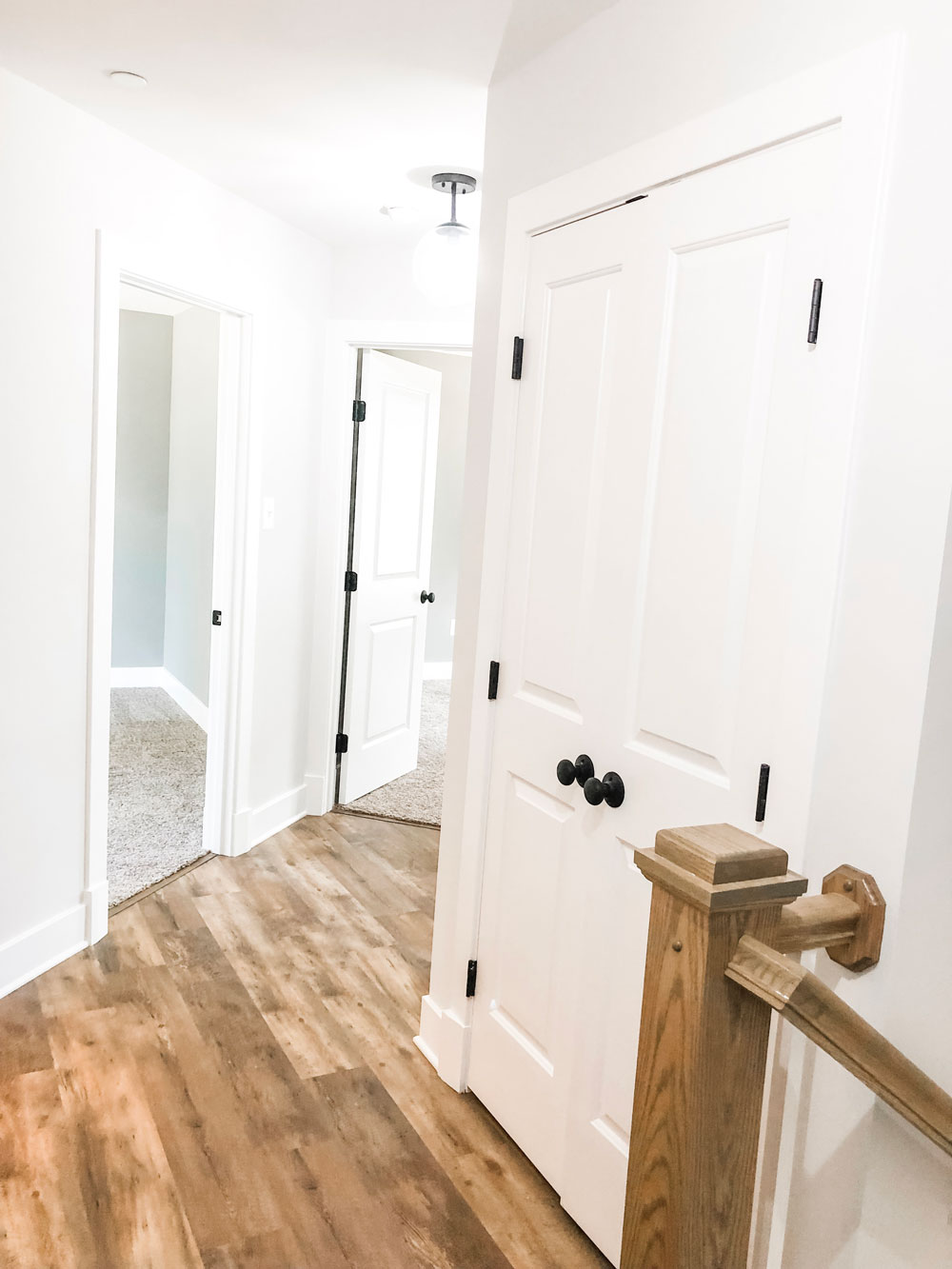 Custom home tour photos. This photo shows the upstairs hallway. The hall has luxury vinyl flooring in a medium tone. There is a large two door linen closet with black knobs.