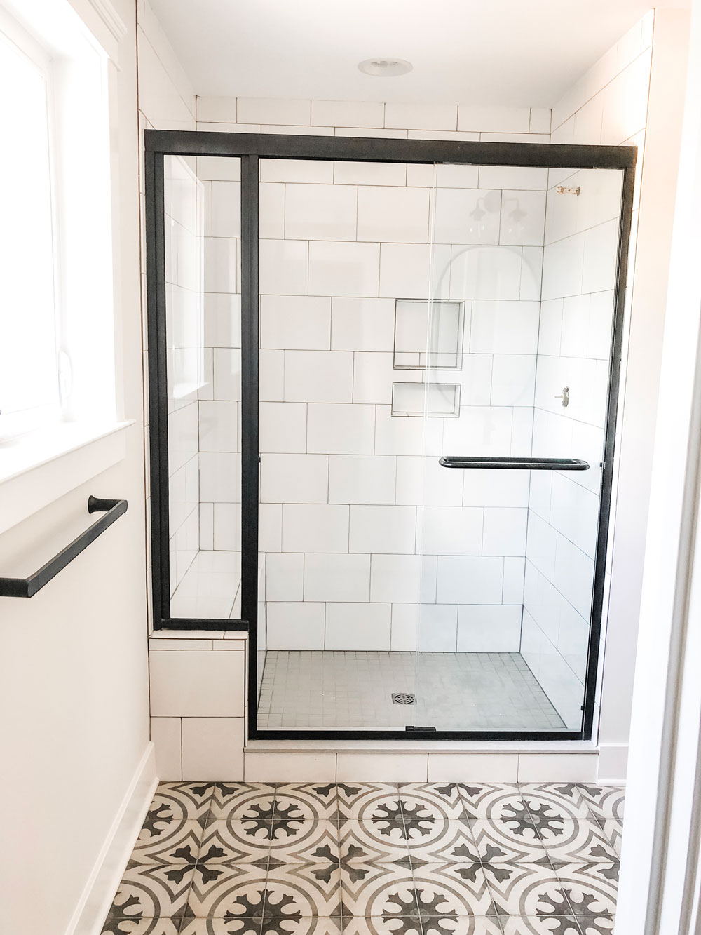 Custom home tour photos. This photo shows the master bath shower. It has a light gray floor tile and large white tiles laid in a subway pattern with gray grout. There is also a black semi-frameless shower door.