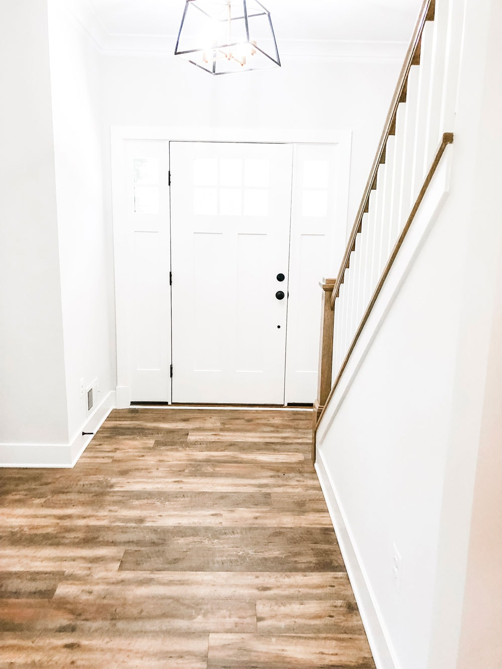 Custom home tour photos. This photo shows the foyer of the home. It has a medium color luxury vinyl wood-looking floor. You can also see the stair rail and the inside of the front door. It is painted white with a black handle.