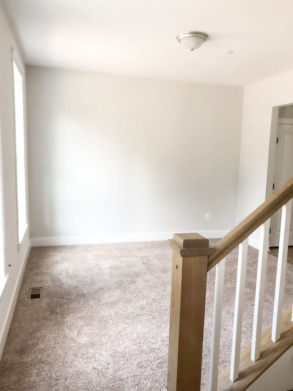 Custom home tour photos. This photo shows the playroom in the home. It has a neutral beige looking carpet, white walls, and a single ceiling light.