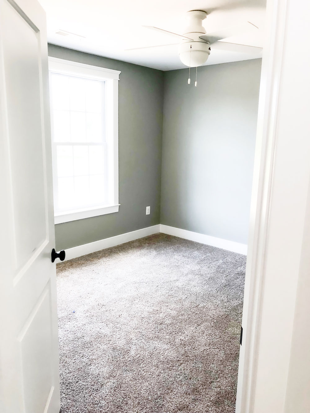 Custom home tour photos. This photo shows one of the two upper bedrooms. It has gray walls and beige carpet. There is a white ceiling fan as well and a large window.