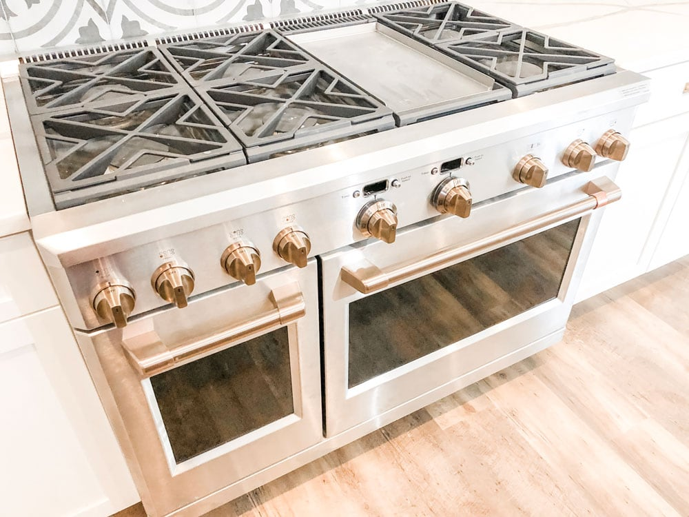 Custom home tour photos. This photo shows the 48 inch GE professional range. It has two ovens. It's stainless steel with gold knobs and handles. It has 6 large burners and a griddle.