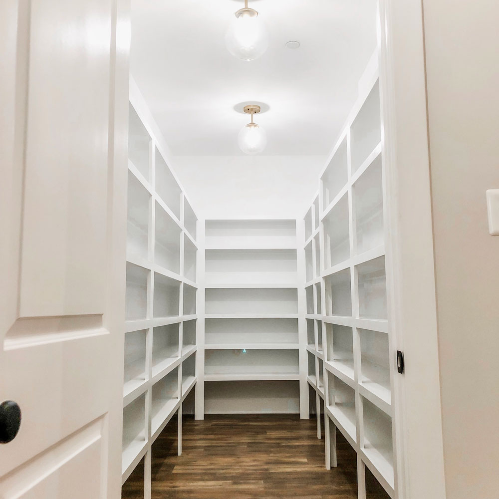 Custom home tour photos. This photo shows the large walk-in pantry.. It has white shelving from floor to ceiling and luxury vinyl flooring that looks like wood.