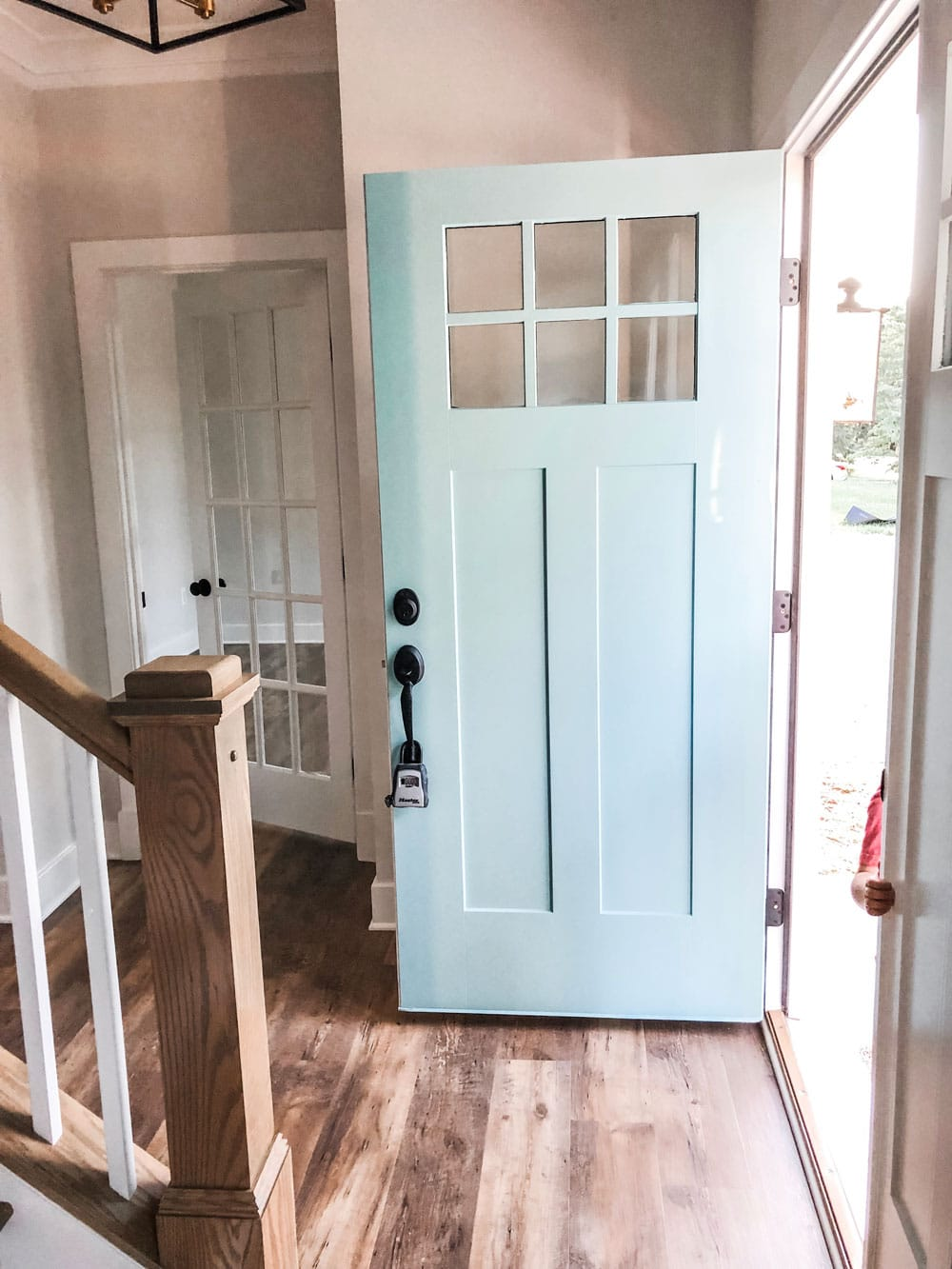 Custom home tour photos. This photo shows the front door opened into the foyer. The front door is a blue color and has a black handle. It has a small 6 pane window at the top of the door.