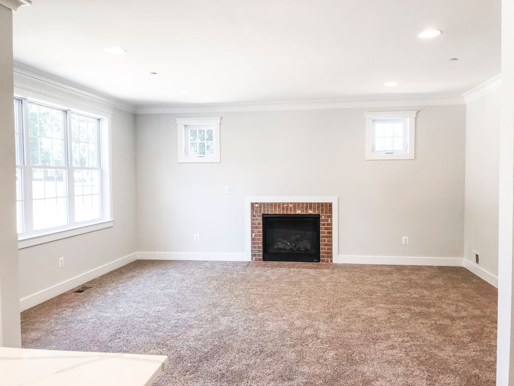Custom home tour photos. This photo shows the family room. It has white walls, a gas fireplace with red brick surround, beige carpet, two small windows up high on either side of the fireplace, and a window located on the left wall. There is white trim and white crown molding.