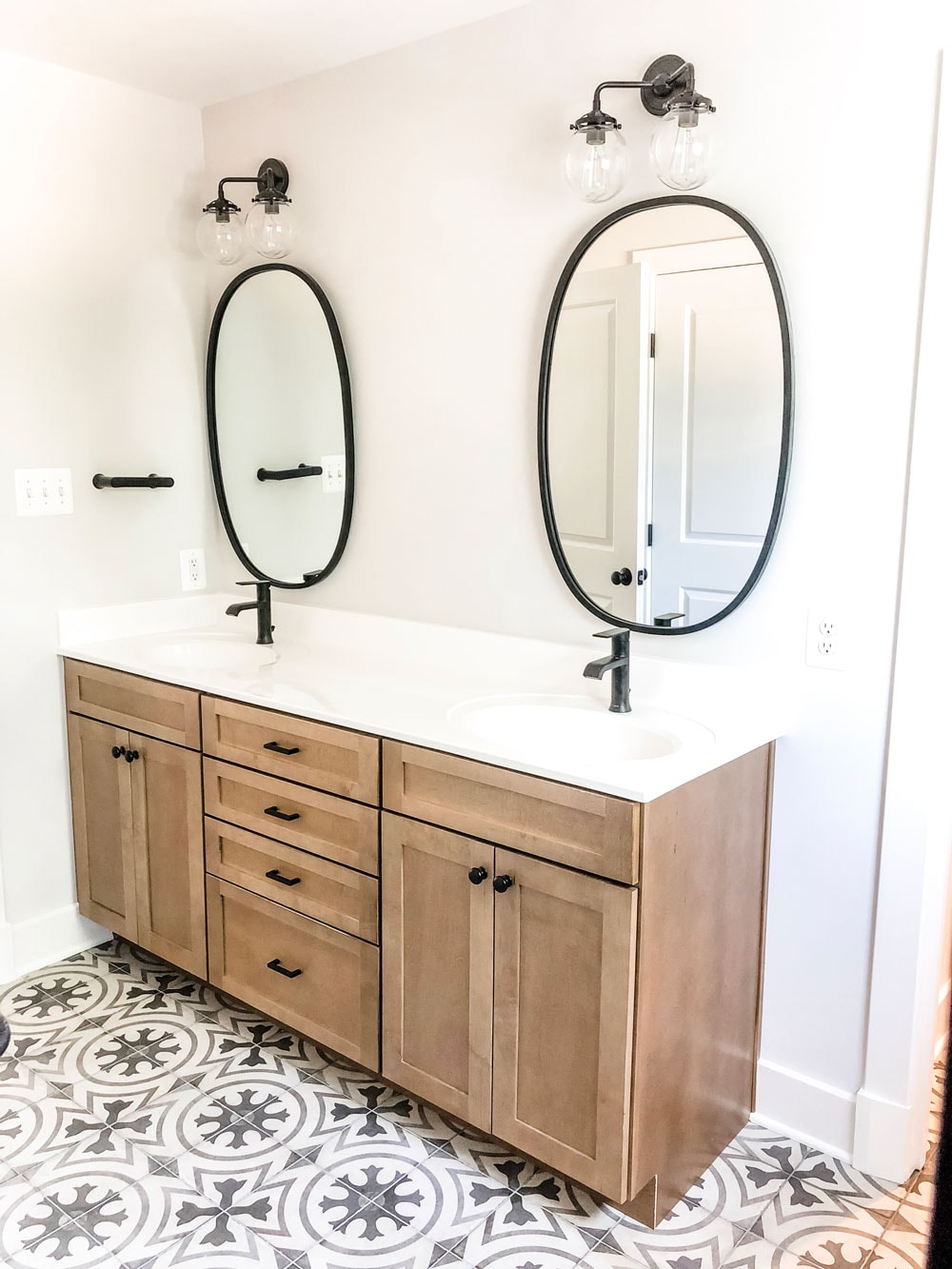 Custom home tour photos. This photo shows the master bathroom with a wood double vanity. The counters are a solid white marble countertop with two sinks. There are two black oval mirrors (one above each sink). There are two black faucets and black hardware on the cabinets. There are also two black lights with glass globes above each mirror.