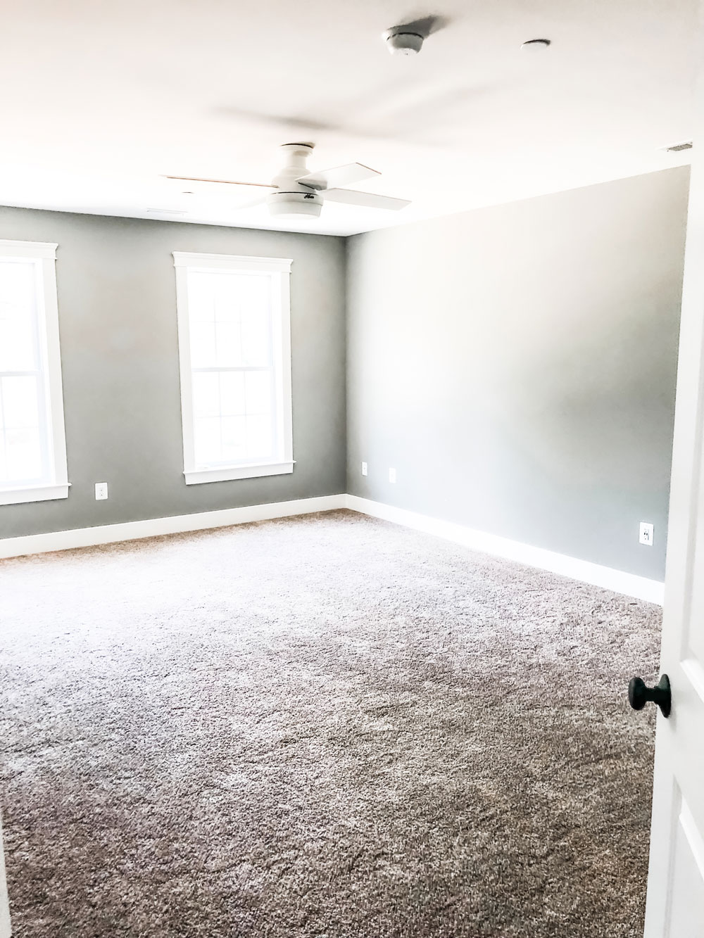 Custom home tour photos. This photo shows the master bedrooms. It has gray walls and beige carpet. There is a white ceiling fan as well and two large windows.