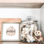 This DIY inexpensive fall wood sign is picture. It's an image of a wood sign with a light wood frame, white background, wood pumpkin, and the words grateful written in black cursive across the pumpkin. A small twine bow is on the stem of the pumpkin. There is also a small fake owl on the far right in front of a glass jar that is filled with dried sticks, leaves, and other outdoor materials in browns and whites.