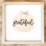 This DIY inexpensive fall wood sign is picture. It's an image of a wood sign with a light wood frame, white background, wood pumpkin, and the words grateful written in black cursive across the pumpkin. A small twine bow is on the stem of the pumpkin.