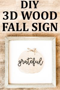 This DIY inexpensive fall wood sign is picture. It's an image of a wood sign with a light wood frame, white background, wood pumpkin, and the words grateful written in black cursive across the pumpkin. A small twine bow is on the stem of the pumpkin. The words, DIY Inexpensive Fall Wood Sign are on the top of the sign.
