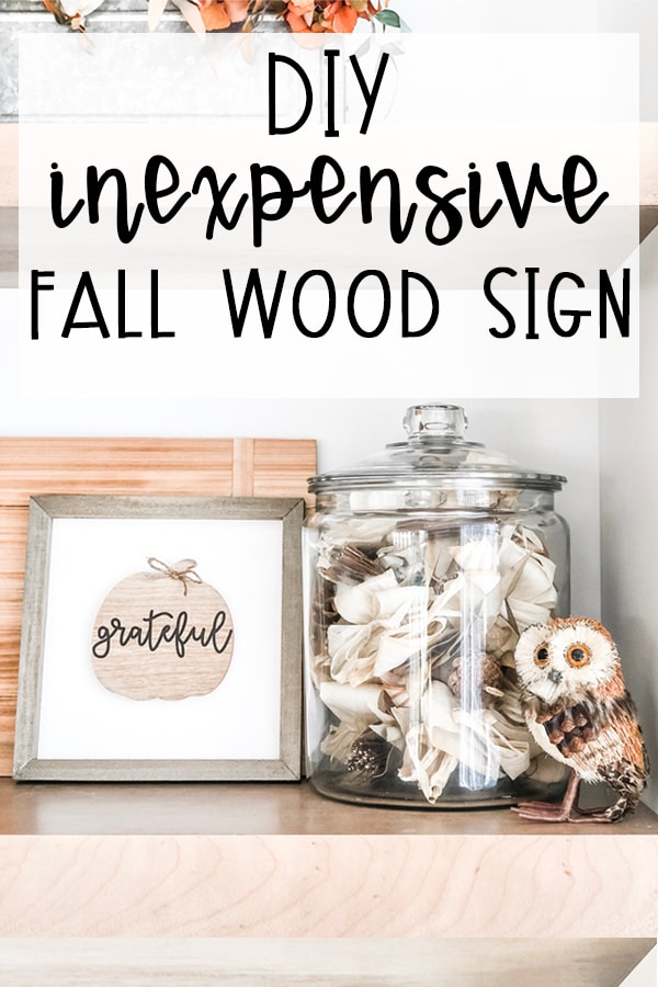 This DIY inexpensive fall wood sign is picture. It's an image of a wood sign with a light wood frame, white background, wood pumpkin, and the words grateful written in black cursive across the pumpkin. A small twine bow is on the stem of the pumpkin. The words, DIY Inexpensive Fall Wood Sign are on the top of the sign. There is also a small fake owl on the far right in front of a glass jar that is filled with dried sticks, leaves, and other outdoor materials in browns and whites.
