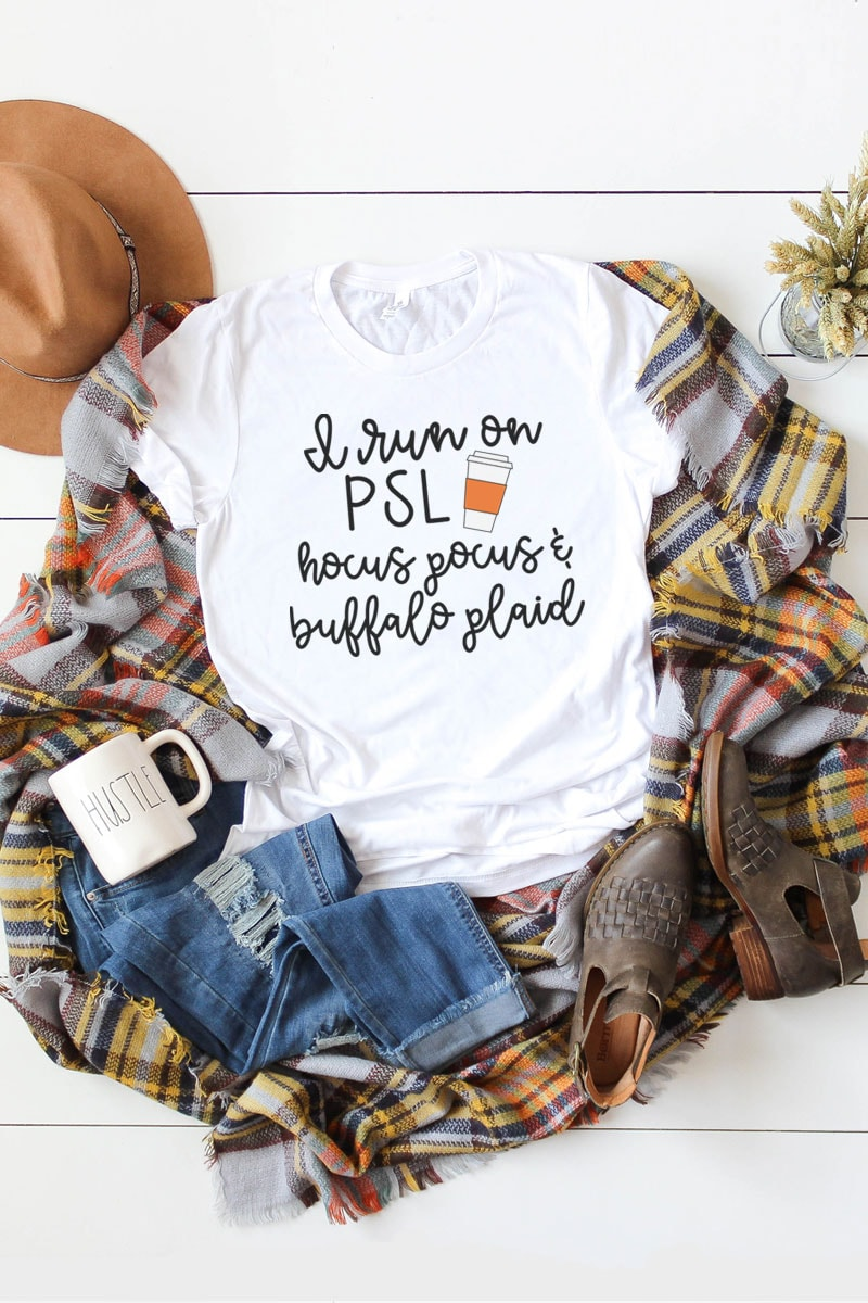 This picture represents an example of the free fall svgs included in this set. This is just one of the options available involving the phrase I Run On... White t-shirt laying on a brown, yellow, orange, and white, plaid blanket. There is a white mug that says hustle in the bottom left on top of a pair of ripped up blue jeans. There are also a pair of brown booties on the far right bottom corner and a tan hat in the top left.