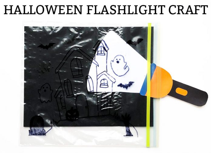 Image of a ziploc bag with a haunted house, ghosts and bats drawn on it. It has a black background in the bag and a flashlight paper placed inside of the bag just in front of the black paper, highlighting one of the ghosts.