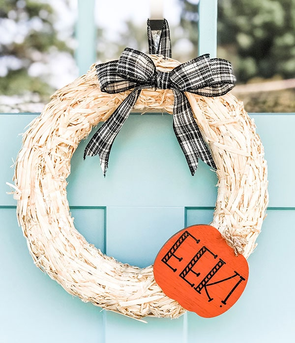 The wreath is on a blue front door, it's made of straw, has a black and white bow at the top, and a bright orange cutout pumpkin with black letters saying, EEK!