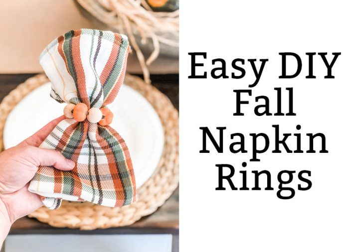 The image is of DIY Thanksgiving napkin rings. They're plaid green, orange, and white napkins with mini pumpkins and wood beads around the napkins. On the right side, the black text on white background says, Easy DIY Fall Napkin Rings.