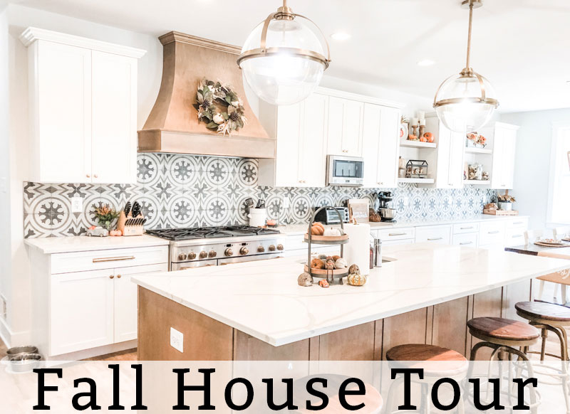 The title fall home tour is at the bottom of the image. Below, is an image of a kitchen. There are two gold and glass pendant lights hanging above an island with a white countertop. The island is a medium wood base. The rest of the cabinets are white. There is a large medium wood hood above the 48 inch stove that is stainless. There is a wreath hanging from the wood hood.