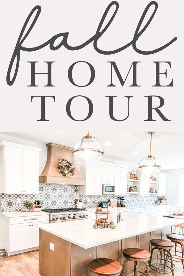 The title fall home tour is at the top of the image. Below, is an image of a kitchen. There are two gold and glass pendant lights hanging above an island with a white countertop. The island is a medium wood base. The rest of the cabinets are white. There is a large medium wood hood above the 48 inch stove that is stainless. There is a wreath hanging from the wood hood.