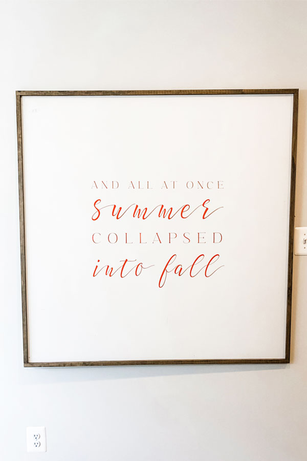Image of a white wood sign on the wall with the quote, And all at once, summer collapsed into fall, in a mix of orange print and script.
