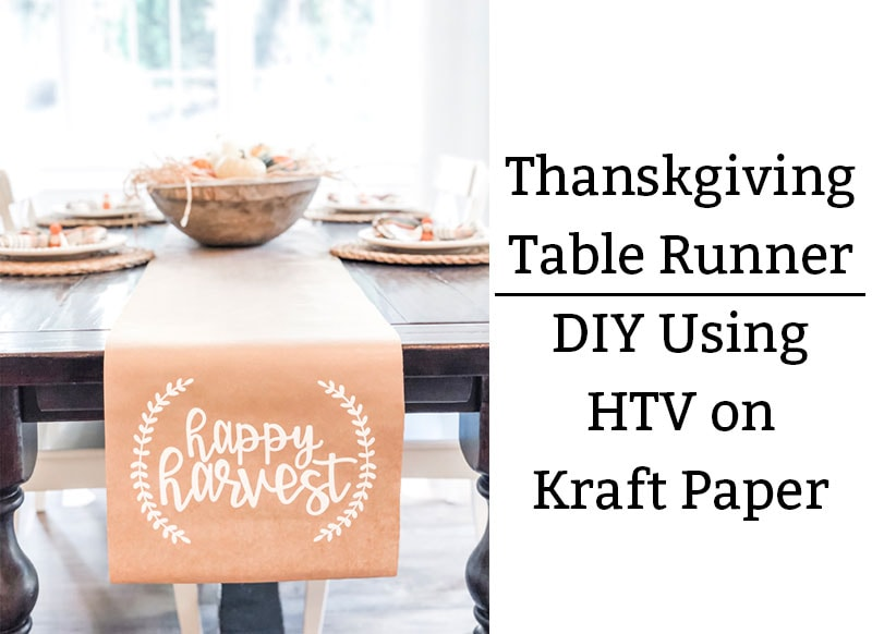 The image shows a kraft paper table runner on a dining table underneath. The words happy harvest are in white on the runner in cursive. There is a small partial wreath on each side of the phrase, happy harvest. On the right side, the phrase in black text says: Thanksgiving Table Runner : DIY Using HTV on Kraft paper.