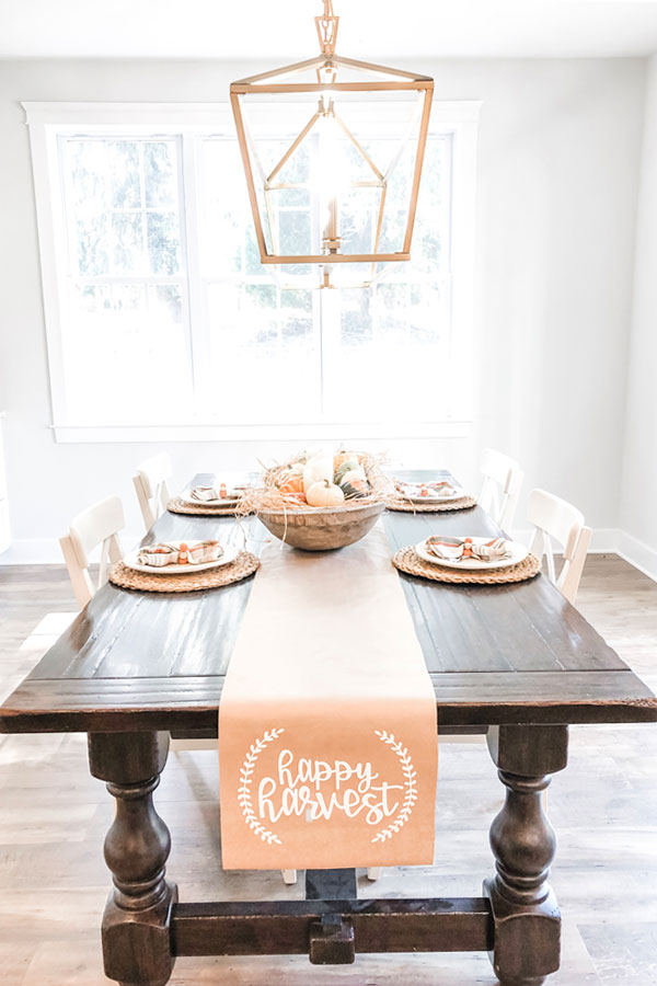 The image shows a kraft paper table runner on a dining table underneath. The words happy harvest are in white on the runner in cursive. There is a small partial wreath on each side of the phrase, happy harvest.