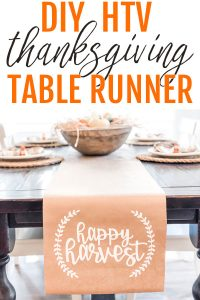 The top of the image says DIY HTV Thanksgiving table runner. It shows a kraft paper table runner on a dining table underneath. The words happy harvest are in white on the runner in cursive. There is a small partial wreath on each side of the phrase, happy harvest.