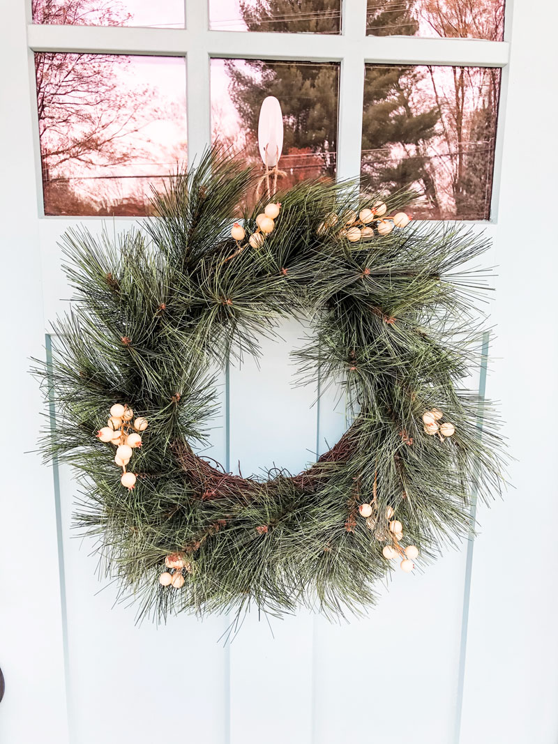 #shop This image shows a green wreath on a blue door. The wreath has small white berry looking clusters on it.