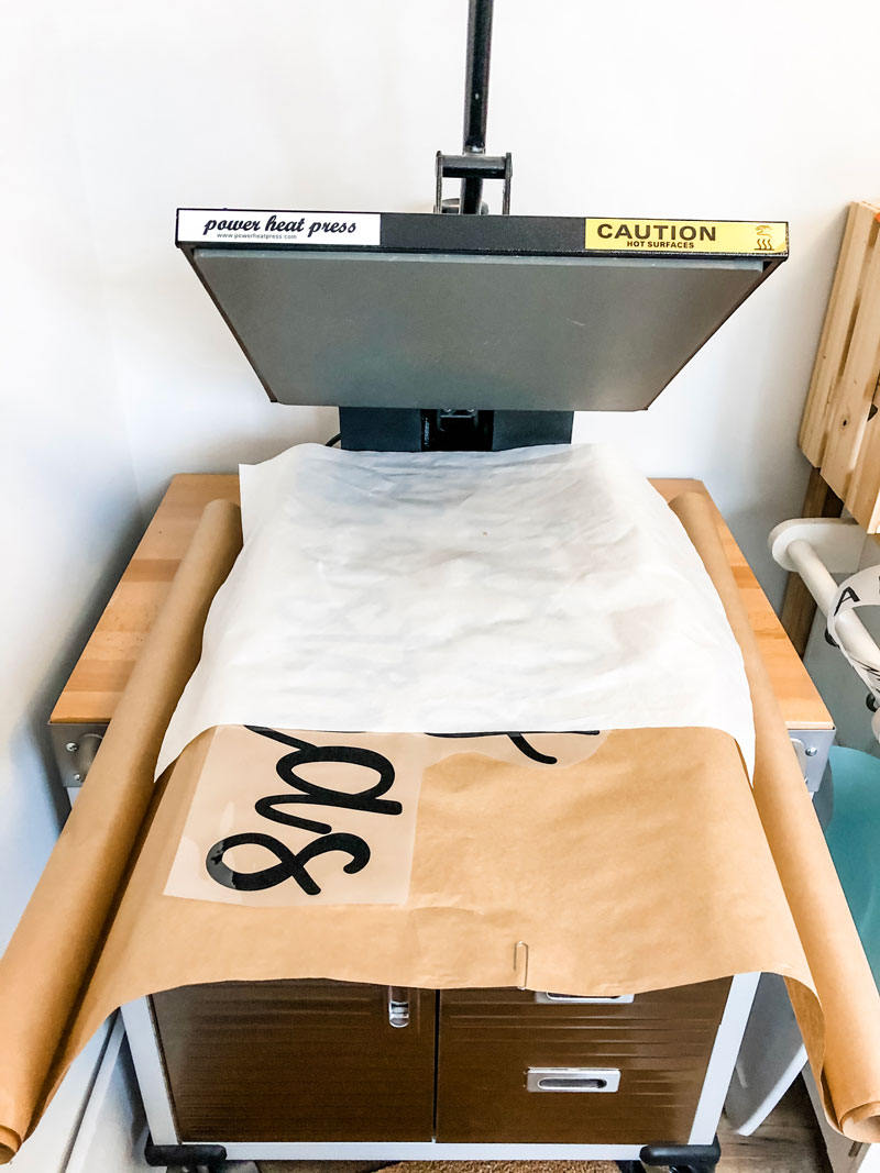 #shop This image shows an open heat press set up with a teflon sheet to press kraft paper with black words.
