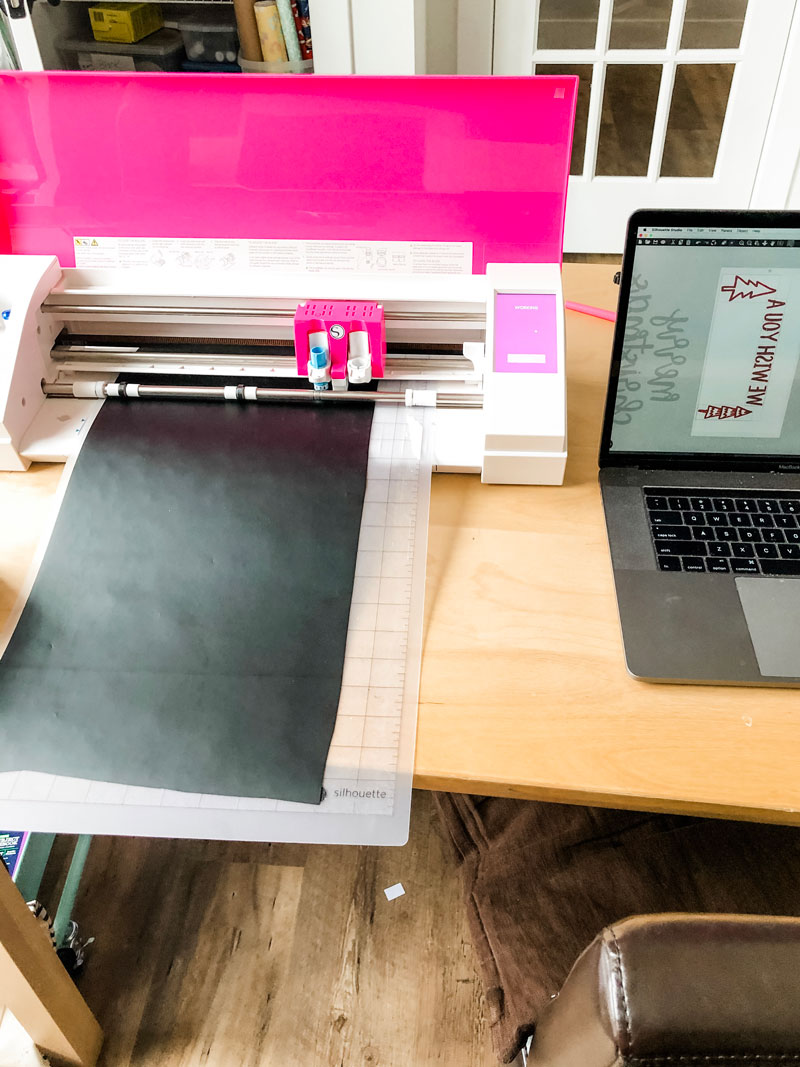 #shop This image shows a pink Silhouette Cameo cutting black vinyl on a cutting mat with a laptop open and a screen opened to a mirrored design saying We wish you a and two trees.