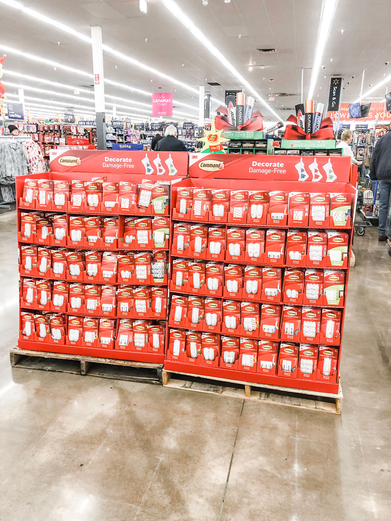 #shop Command™ hook display in walmart. The display is a red cardboard display full of clips, hooks, and strips.