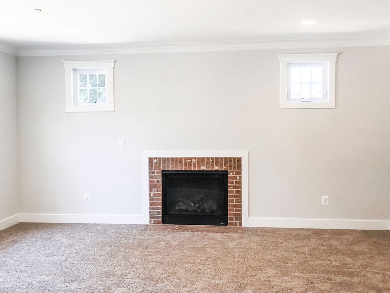 #shop this image shows a brick fireplace with white walls and two small windows up above to the right and left of the fireplace.