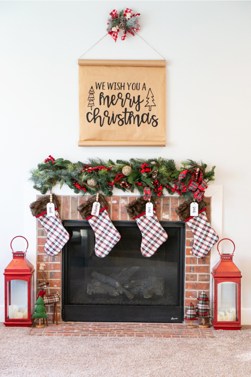#shop This image shows a brick fireplace surround with two large red lanterns sitting on the ground on either side. Four stockings are hung above the fireplace with a garland above that. Above the garland is a sign with black letters on kraft paper saying: we wish you a Merry Christmas. There is a swag of greenery and a red and white checkered bow. Next to the red lanterns on the floor are a green and red plaid reindeer, green tree, and two plaid trees. Each stocking has a name hanger in white that say: Dad, Mommy, Carl, Jack.