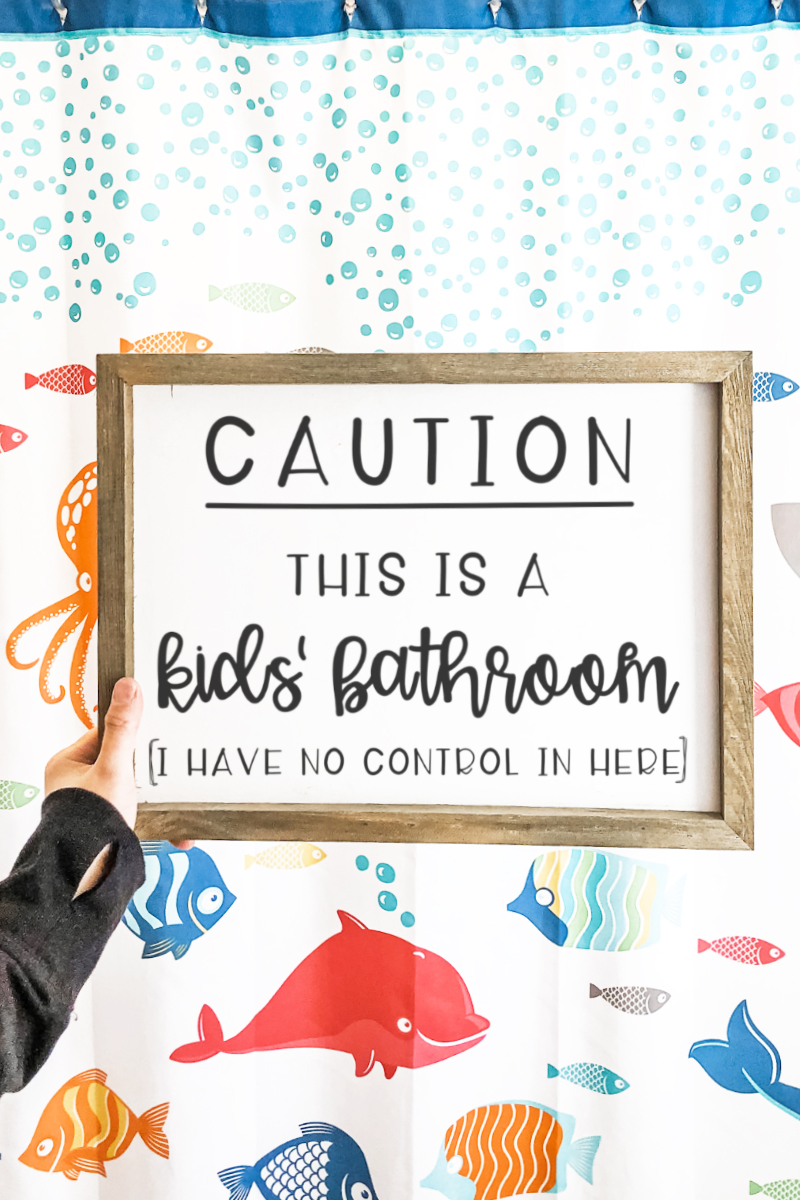 Funny Bathroom SVG and Print at the top in black text with a white background. Below it is a white sign with a wood frame. The sign in black text reads: Caution this is a kids' bathroom (I have no control in here). The background behind the sign is a white shower curtain with brightly colored fish and blue bubbles.