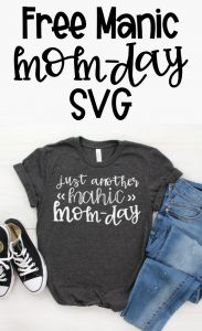 Free Manic Mom Day SVG is on the top in black text on a white background. To the bottom is an image of a gray t-shirt with the words, Just another Manic Mom-Day. Next to a pair of blue jeans and black converse sneakers.