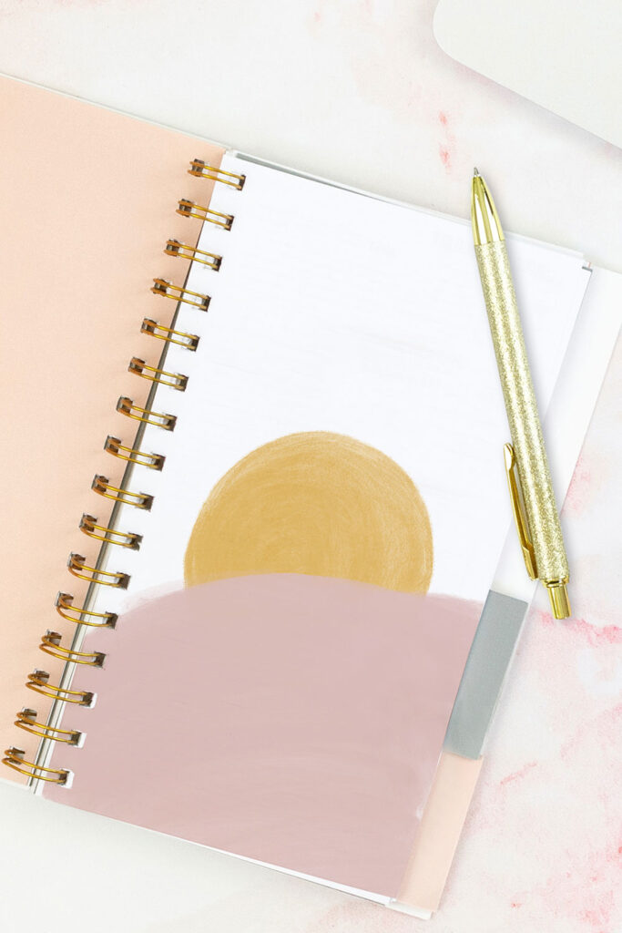 Open pink planner with an abstract divider showing a yellow sun with a large pink cloud-like shape overtop of it. With a gold pen on top of the planner.