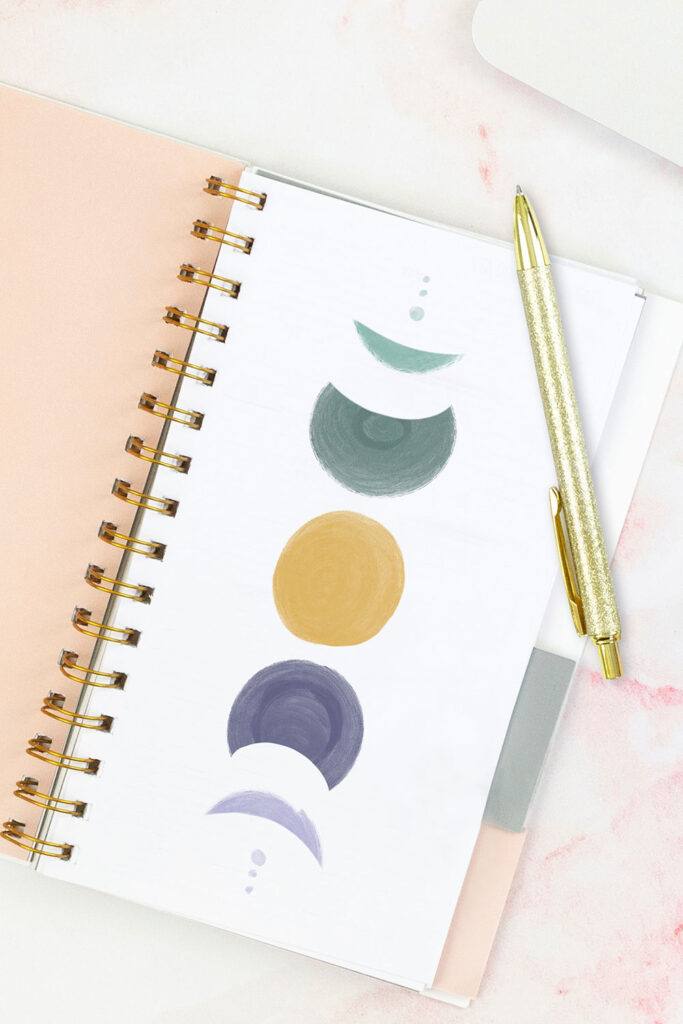 Open pink planner with an abstract divider showing a yellow moon in the center with two 3/4 moons on either side in purple and green, and then two crescent moons on either side in purple and green, and two tiny circles in green and purple on either side of that . With a gold pen on top of the planner.