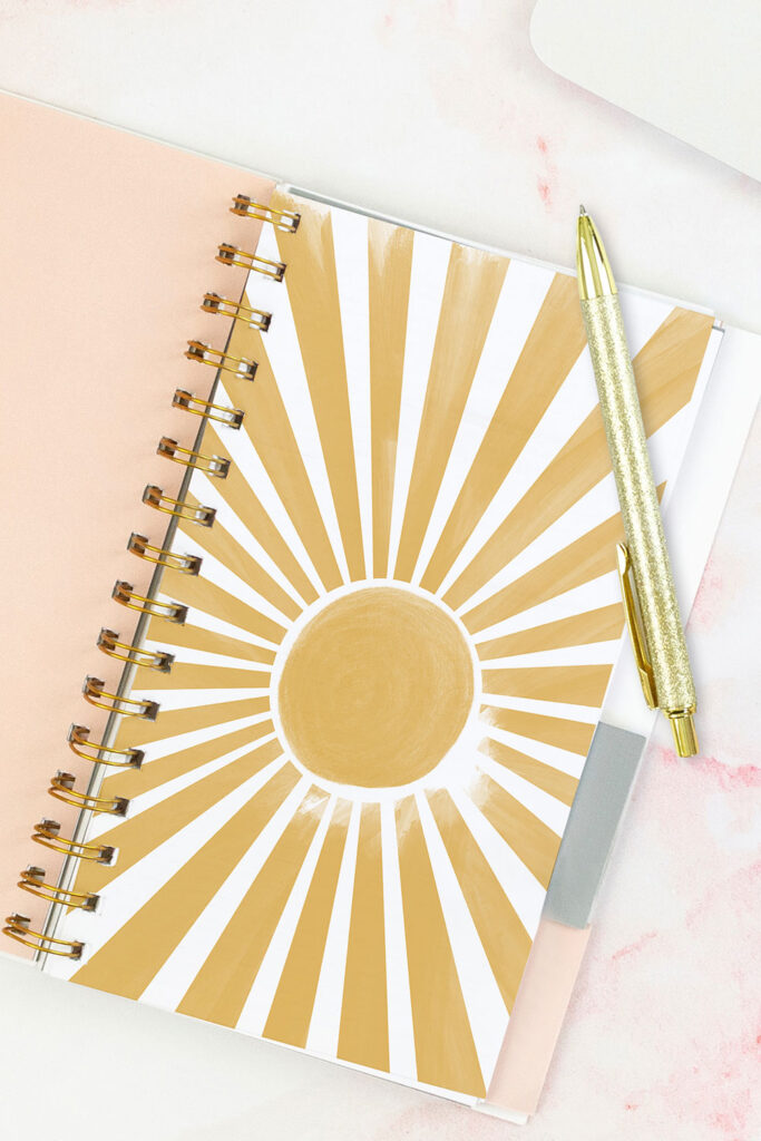 Open pink planner with an abstract divider showing a yellow sunburst. With a gold pen on top of the planner.