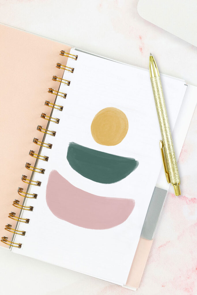 Open pink planner with an abstract divider showing a yellow sun over top of an abstract green shape similar to a bowl or half-circle, and a pink abstract shape also shaped like a bowl or half-circle. With a gold pen on top of the planner.