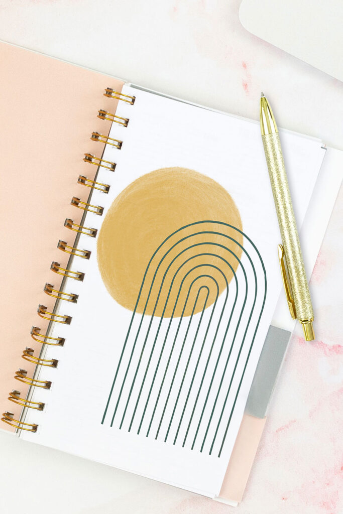Open pink planner with an abstract divider showing a yellow sun and a dark blue rainbow. With a gold pen on top of the planner.