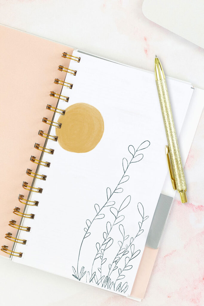 Open pink planner with an abstract divider showing a yellow sun and green plant. With a gold pen on top of the planner.