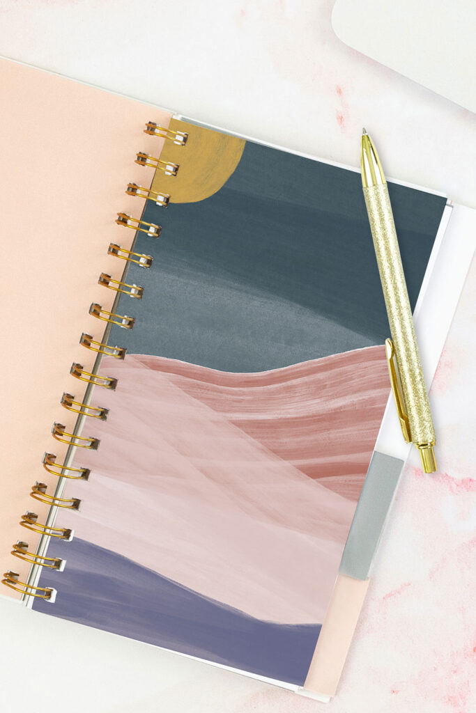 Open pink planner with an abstract divider showing a yellow moon, dark blue sky, and pink/purple mountains. With a gold pen on top of the planner.