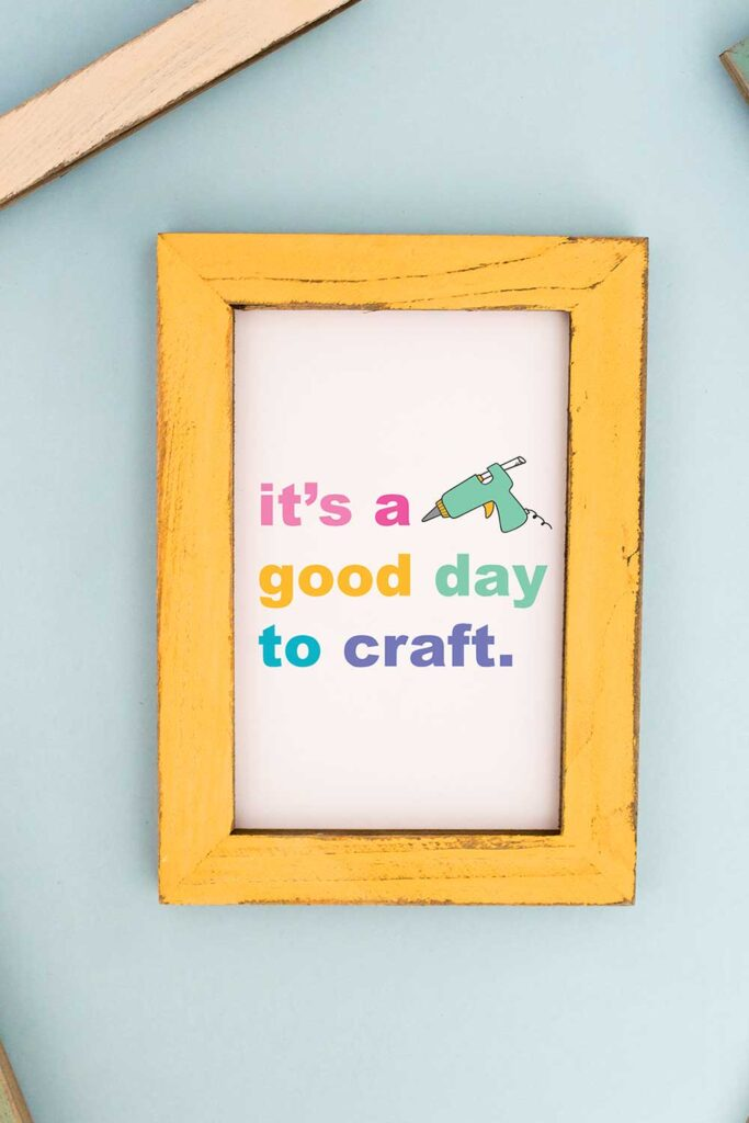 Blue background with a yellow picture frame. The inside of the picture frame says it's a good day to craft with the picture of a hot glue gun.