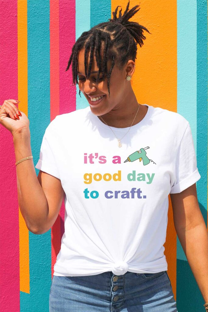Woman standing in a white t-shirt and jeans smiling and looking off to the side. She has one arm down to her side and another raised. She's up against a bright, colorful striped background. Her t-shirt says it's a good day to craft with a glue gun.