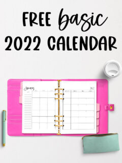 The image shows the 2022 Free Printable Calendar you can download. At the top of the image are the words Free Basic 2022 Calendar in black overlaid over light gray background. The image is of an open planner with a bright pink cover. Inside of the planner are pink tab dividers and it's open to a two page January 2022 calendar. On the top right is the lid of a white travel mug. To the bottom left next to the open planner is a mint green and gold pen. Below the planner to the bottom right is a mint green pencil pouch with a gold zipper. The pouch is zipped open.