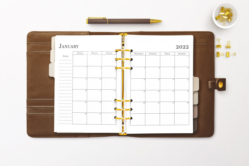 A brown leather planner lays open. Inside is a January 2022 calendar spread in black text on white paper. There are gold rings in an A5 style. A brown pen sits just above the planner. To the right are gold binder clips in a small bowl and four lay on the table below the bowl.